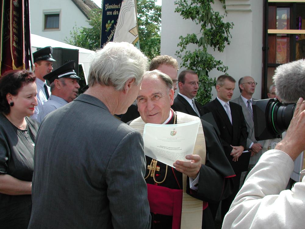 Bischof Manfred Müller aus Regensburg überreicht die Einweihungsurkunde